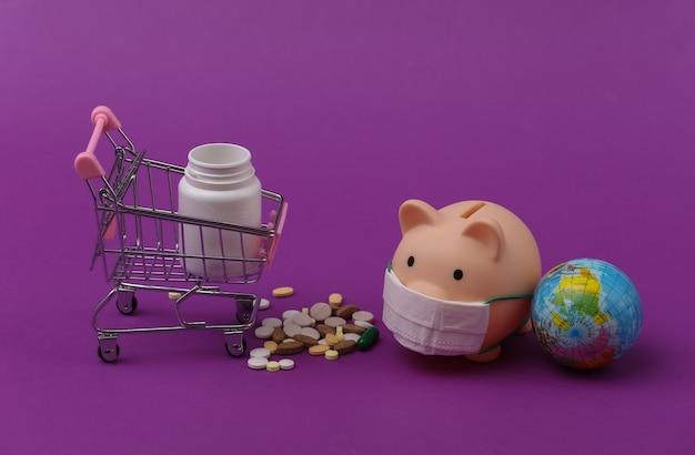 Salvadanaio in maschera medica e carrello della spesa con bottiglia di pillole, globo su sfondo viola.