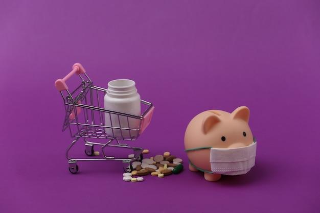 Salvadanaio in maschera medica e carrello della spesa con bottiglia di pillole su sfondo viola.