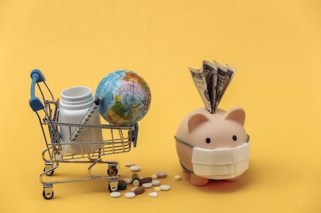 Salvadanaio in maschera medica e carrello della spesa con bottiglia di pillole, siringa su sfondo giallo. pandemia di covid-19