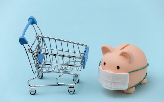 Salvadanaio in una maschera medica con un carrello della spesa su sfondo blu. aumento dei prezzi, shopping durante il covid-19, crisi economica, economia