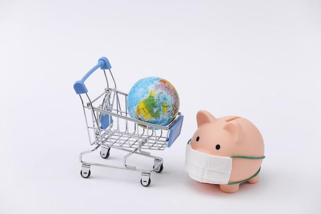 Salvadanaio in una maschera medica con un carrello della spesa, globo su sfondo bianco. shopping durante covid-19, crisi economica, economia