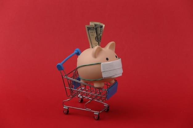 Salvadanaio in una maschera medica con un carrello della spesa su sfondo rosso. shopping durante covid-19, crisi economica, economia