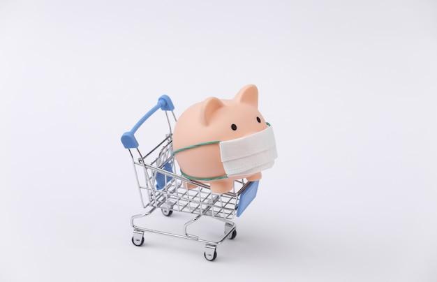Salvadanaio in una maschera medica con un carrello della spesa su sfondo bianco. shopping durante covid-19, crisi economica, economia