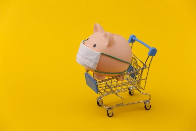 Salvadanaio in una maschera medica con un carrello della spesa su sfondo giallo. shopping durante covid-19, crisi economica, economia