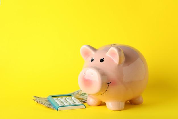 Porcellino salvadanaio, soldi e calcolatore su superficie gialla