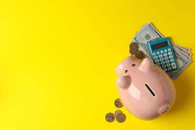 Porcellino salvadanaio, soldi e calcolatore sulla vista gialla e superiore
