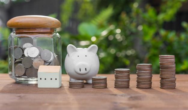 Salvadanaio, monete di denaro e modello di casa sulla tavola di legno con la natura sul concetto di blu, risparmio e investimento