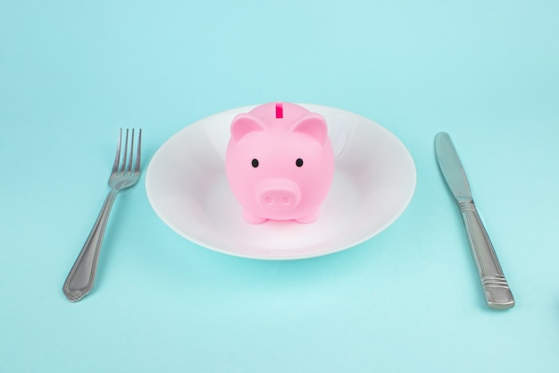Salvadanaio sul piatto con forchetta e coltello, concetto di risparmio del consumatore. risparmi sulla spesa, spese alimentari