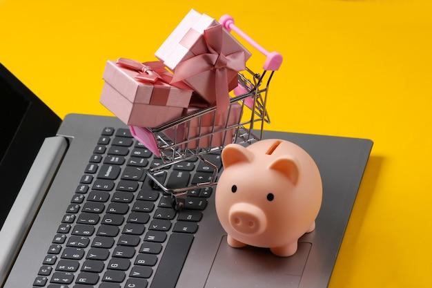 Salvadanaio, carrello della spesa con scatole regalo sul primo piano della tastiera del computer portatile