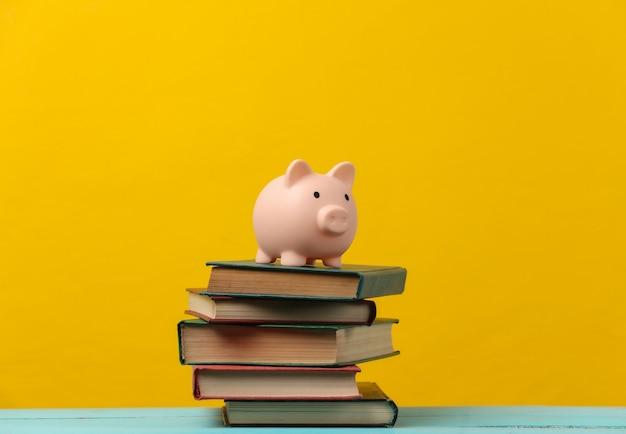 Salvadanaio su una pila di libri. giallo