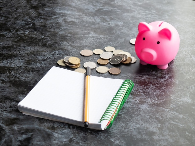 Un salvadanaio si trova su un tavolo con monete sparse e un blocco note