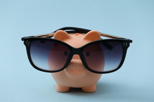 Salvadanaio in occhiali da sole su un blu