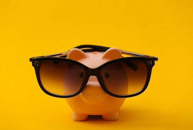 Salvadanaio in occhiali da sole su un giallo