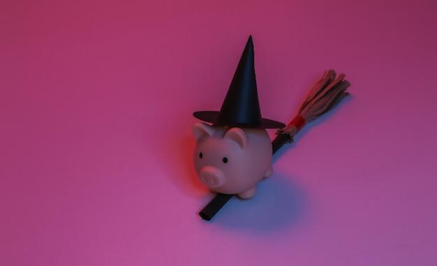 Salvadanaio con un cappello da strega su un manico di scopa. luce al neon sfumata rosso-blu. tema di halloween
