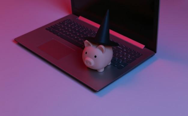 Salvadanaio con un cappello da strega sulla tastiera del laptop. luce al neon sfumata rosso-blu. tema di halloween