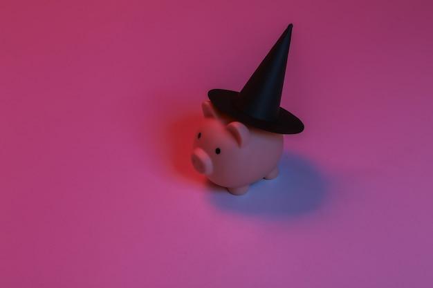 Salvadanaio con un cappello da strega. luce al neon sfumata rosso-blu. tema di halloween