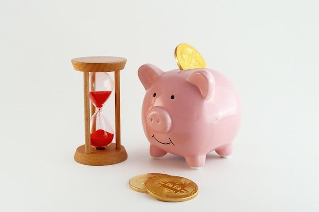 Salvadanaio con monete bitcoin e clessidra isolati