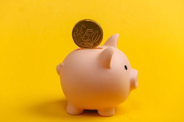 Salvadanaio con moneta su giallo.