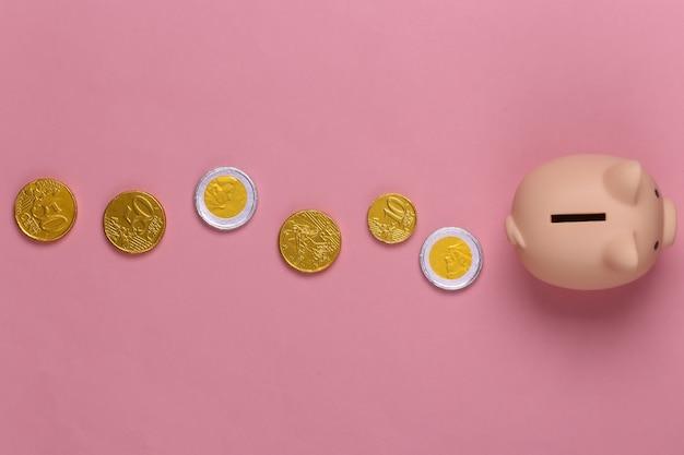 Salvadanaio con monete su pastello rosa