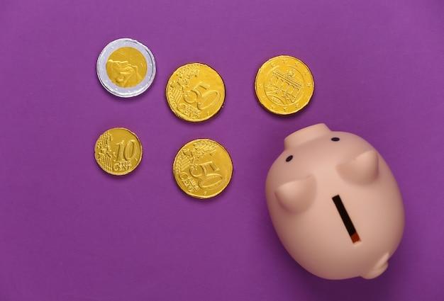 Salvadanaio con monete su viola