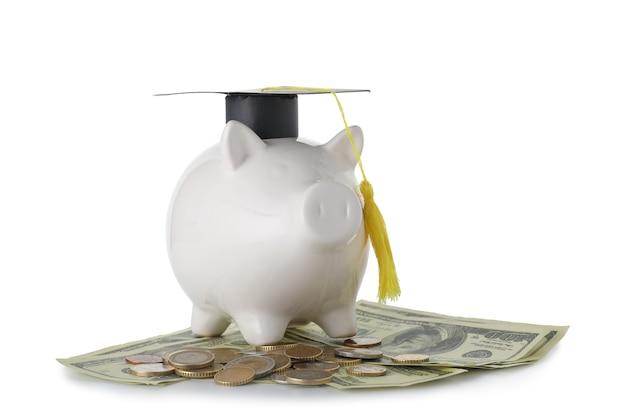 Salvadanaio con cappello di laurea e soldi su sfondo bianco. concetto di tasse scolastiche