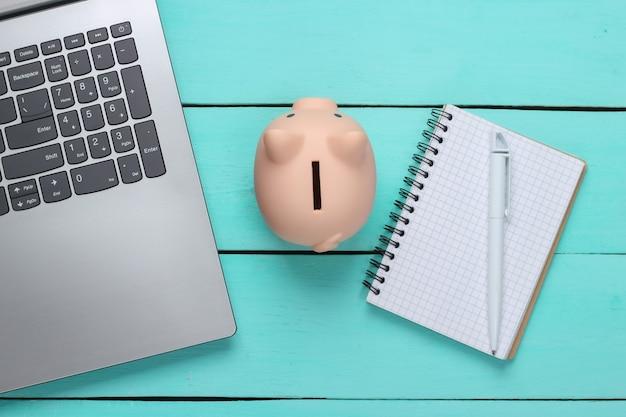 Salvadanaio con laptop, taccuino sulla superficie di legno blu. fare soldi online o concetti di business su internet. vista dall'alto. lay piatto