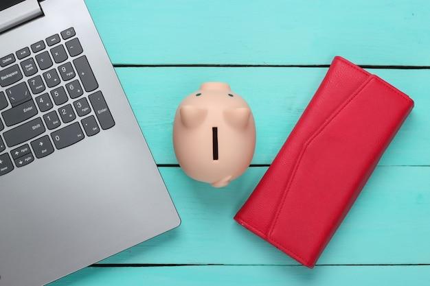 Salvadanaio con laptop, portafoglio su superficie di legno blu. fare soldi online o concetti di business su internet. vista dall'alto. lay piatto