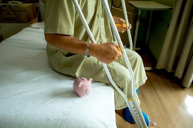Un salvadanaio con la gamba di un uomo usa le stampelle per camminare dopo un intervento chirurgico recupero lesioni ossa rotte.