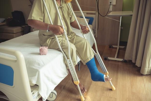 Un salvadanaio con la gamba di un uomo usa le stampelle per camminare dopo un intervento chirurgico di recupero con le ossa rotte