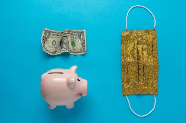 Salvadanaio con una maschera medica e banconota da un dollaro sgualcita