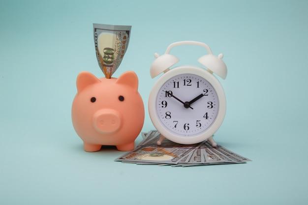 Salvadanaio con banconote di denaro e sveglia su sfondo blu. il tempo è il concetto di denaro
