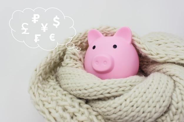 Salvadanaio con soldi e sciarpa con valute mondiali ologramma digitale nel cloud pensato sopra la sua testa su sfondo blu. risparmio finanziario ed economia bancaria.