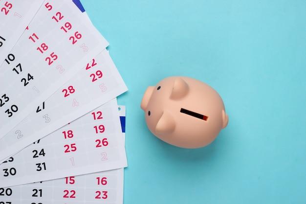 Salvadanaio con un calendario mensile su un blu. pagamento di alloggi in affitto o prestiti.