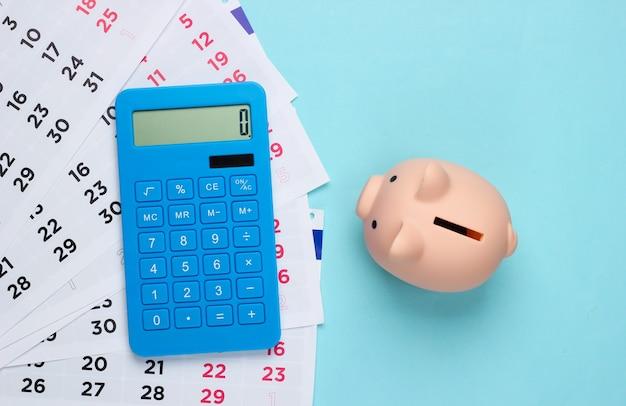 Salvadanaio con calendario mensile, calcolatrice su un blu. pagamento di alloggi in affitto o prestiti
