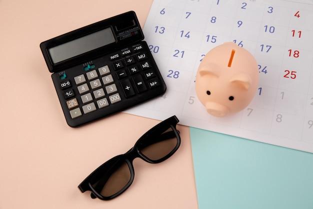 Salvadanaio con calendario mensile, calcolatrice. pagamento di alloggi in affitto o prestiti.