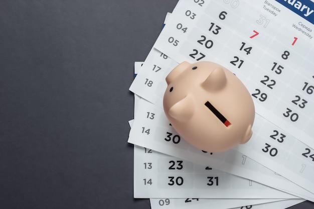 Salvadanaio con calendario mensile su una superficie grigia. budget mensile. vista dall'alto