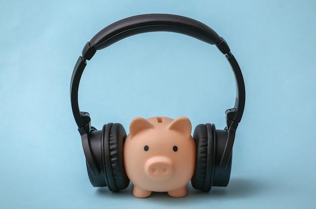 Salvadanaio con cuffie stereo per ascoltare musica su sfondo blu