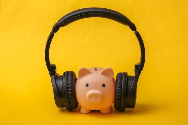 Salvadanaio con cuffie stereo per ascoltare musica su sfondo giallo