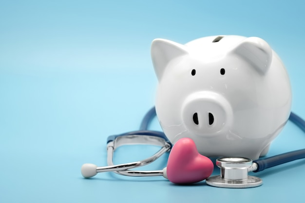Salvadanaio con stetoscopio su blu controllo finanziario dell'assistenza sanitaria che salva il concetto di assicurazione medica