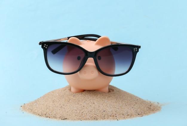 Salvadanaio con occhiali da sole sull'isola di sabbia. viaggio, concetto di vacanza al mare