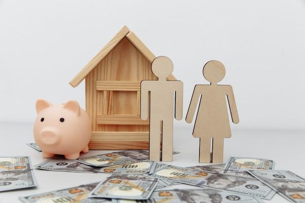Salvadanaio e famiglia in legno con casa