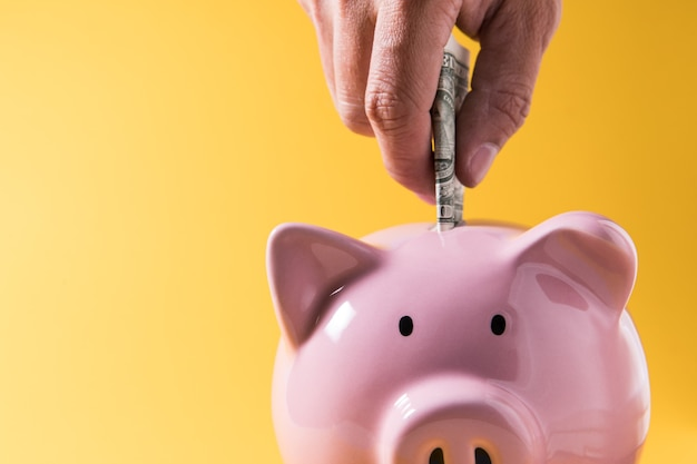 Salvadanaio su sfondo giallo per economia, risparmio di ricchezza di denaro e concetto finanziario