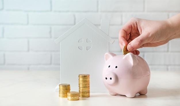 Salvadanaio salvadanaio, moneta e modello di casa su bianco