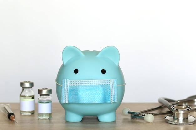 Piggy con indossare maschera medica protettiva e termometro con bottiglia di medicina su sfondo bianco, risparmiare denaro per l'assicurazione medica e il concetto di assistenza sanitaria, vaccino contro il coronavirus