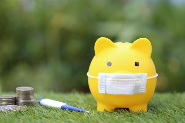 Piggy con maschera medica protettiva da portare e termometro con pila di monete soldi su uno spazio verde naturale