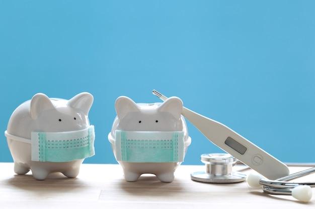 Piggy con maschera medica protettiva da indossare con stetoscopio su sfondo verde, risparmiare denaro per l'assicurazione medica e il concetto di assistenza sanitaria