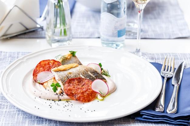 Filetto di lucioperca con chorizo, cavolfiore e ravanello in un ristorante che serve. avvicinamento. keto, paleo, cibo dietetico fodmap.