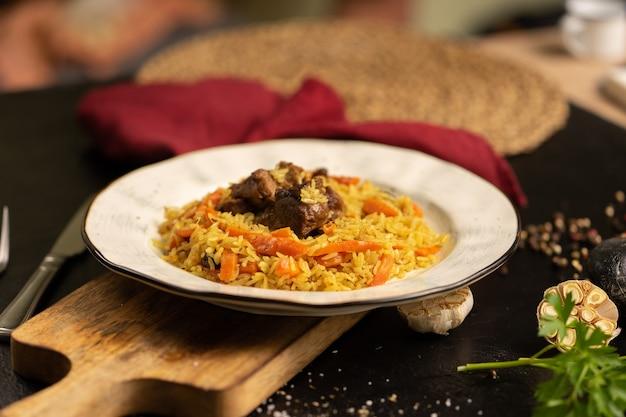 Pilaf con agnello e carote. piatto orientale caldo tradizionale di riso di agnello e verdure decorato con prezzemolo e aglio su una tavola nera.