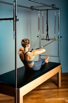 Letto del riformatore di pilates, concetto dell'ormone del corpo pilates, donna e istruttore che fanno esercizi sul riformatore del simulatore per il trattamento del sistema muscolo-scheletrico