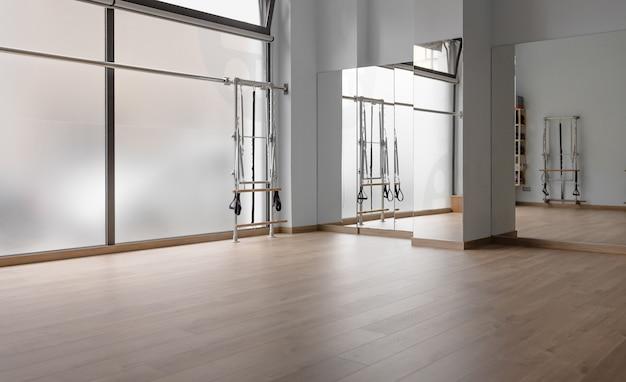 Angolo studio pilates dove si può vedere un pavimento in legno, una grande finestra, uno specchio e una macchina pilates
